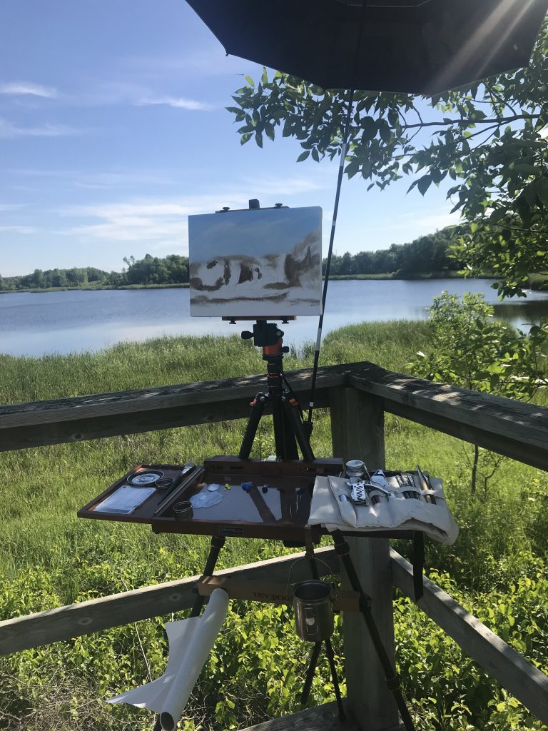 Plein air set up with umbrella, tripod, and palette.